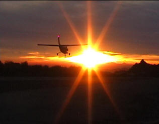 airplane lands into the sunset